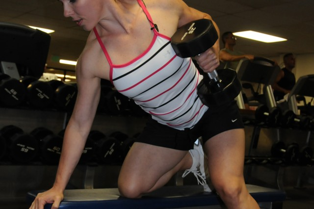 Christina Mace cranks out a set of one armed dumbbell rows at the Hickam Air Force Base gymnasium during a routine morning workout.  Mace, a former Soldier and Army spouse, won the women's overall title at the 2009 Armed Forces Hawaii Bodybuilding Championships April 25 at Naval Station Pearl Harbor.