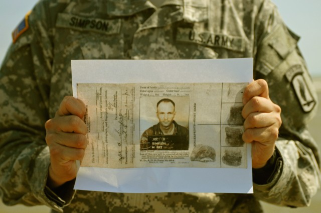 Pfc. Scott Simpson, a medic with Headquarters Company, 173rd Airborne Brigade Combat Team, holds a copy of his grandfather's military identification card from World War II on Normandy's Utah Beach, June 4. His grandfather landed on the beach with the 4th Infantry Division as part of the third wave of Operation Overlord, on June 6, 1944.