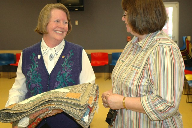 Suzane Ayers, mother of Cpl. John Ayers, cradles a quilt given to her by Debbie Yff, Georgia coordinator for Home of the Brave Quilts.