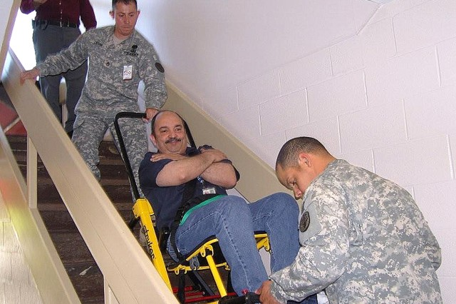 "Medic Staff Sgt. Jaime Leon (top) with the help of his medic partner move an ""exercise patient"" down the stairs during an evacuation drill May 21. The patient, Armando Baez, was transported in the Stryker Stair Chair, which helps maneuver patients up and down the stairs. The chair can hold up to 500 pounds."