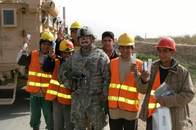Navy Lt. j.g. William Moiles stands with a group of Civil Service Corps students after distributing comfort items at one of the work sites.  Moiles saw this as a way to build relationships and reward the students for their performance