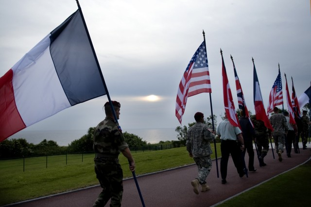 Participants at the 65th anniversary of D-Day carry flags early in the morning at the American Cemetery overlooking Omaha Beach in Normandy, France.