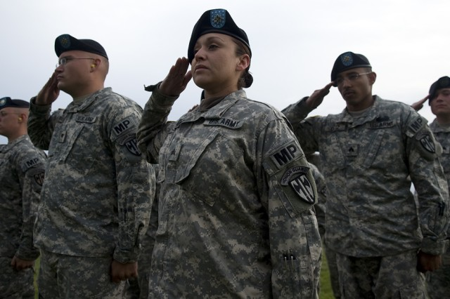 Sgt. Marlene Cerna pays respects during the playing of the U.S. national anthem as part ceremonies for the 65th anniversary of D-Day. Cerna is a member of the U.S. Army Salute Battery Team, 529th Military Company, U.S. Army Garrison Heidelberg, Germany.