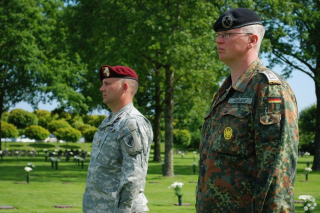 """Army Reserve Maj. John M. Fisher, left, a member of the U.S. Army Civil Affairs and Psychological Operations Command (Airborne), stands side-by-side with his German counterpart along with over 30 German, American, British and French World War II veterans, to honor the fallen and commit to a partnership for peace here, June 5. Over 200 people attended the commemoration service. """""""