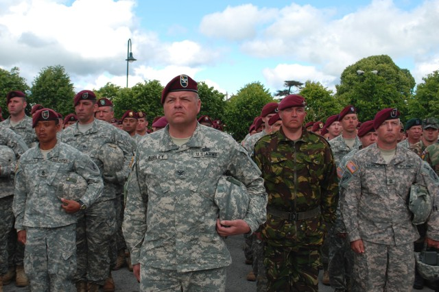 """Army Reserve Col. Edward Burley, commander of the 2nd Psychological Operations Group (Airborne), a part of the U.S. Army Civil Affairs and Psychological Operations Command (Airborne), stands in front of Army Reserve paratroopers and British PARAS from the 4th Battalion, a Territorial Army battalion of the parachute regiment consisting of volunteers who have civilian employment. The Soldiers were taking part in commemorative ceremonies at the St. Mere Eglise square for the 65th Anniversary of the D-Day landings at Normandy. """""""