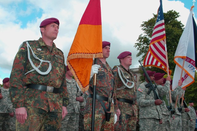 """German paratroopers, wearing their newly earned U.S. Airborne wings, stand side-by-side paratroopers from the U.S. Army Civil Affairs and Psychological Operations Command (Airborne) in front of the church at St. Mere Eglise here, June 6. Soldiers from various countries were taking part in commemorative ceremonies at the square for the 65th Anniversary of the D-Day landings at Normandy. """""""