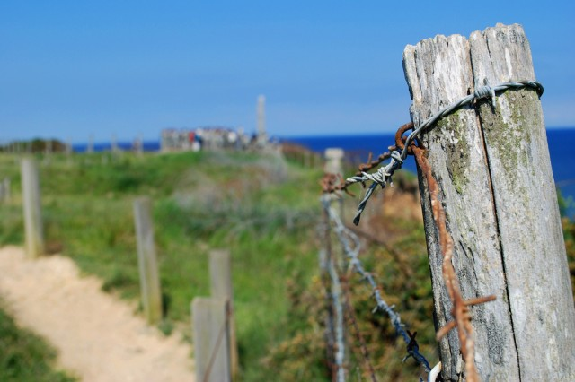"""View of barbed wire fences along the top of Pointe-Du-Hoc with the Ranger monument in the background here, June 5. The Rangers scaled the sheer cliffs to take out this German gun turret that watches over the coast. Today the site has a granite memorial to honor the 2nd Ranger Battalion and their heroic assault. The U.S. Army Civil Affairs and Psychological Operations Command (Airborne) is the sole airborne command within the U.S. Army Reserve and is supporting the 65th D-Day Anniversary ceremonies. """""""