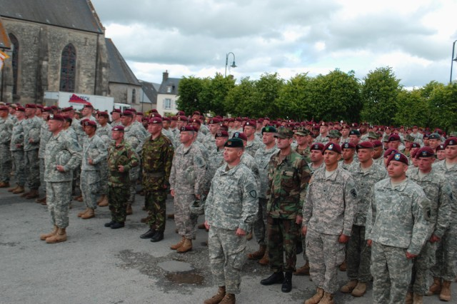 """Soldiers from various U.S. and foreign commands, including the U.S. Army Civil Affairs and Psychological Operations Command (Airborne) and the Special Operations Command Europe, stand in front of the church at St. Mere Eglise here, June 6. The Soldiers were taking part in commemorative ceremonies at the square for the 65th Anniversary of the D-Day landings at Normandy. """""""