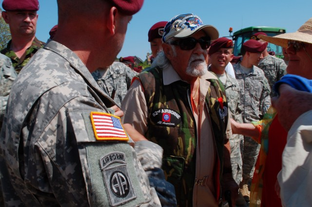 """Soldiers with the 82nd Airborne Soldiers take time to meet Second World War veteran Julius Eisner here on June 5. Eisner was a pathfinder with 'D' Company, 2nd Battalion, 505th Parachute Infantry Regiment, 82nd Airborne Division. He was one of the first paratroopers on the ground on D-Day and jumped in around 1:21 am, June 6, 1944, Drop Zone 'Oscar', near St. Mere Eglise, approximately 30 minutes before the main assault body. This particular regiment was one of the few who actually landed where they were supposed to land. He shared stories of the old 82nd Airborne Division and is a living inspiration to a whole new generation of airborne paratroopers. """""""