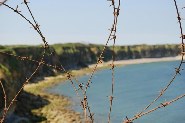 """The view of the beaches of Normandy through the barbed-wire fence that lie atop of Pointe-du-Hoc on June 5. On D-Day the 2nd Ranger Battalion scaled the sheer cliffs to take out the German casemate that watches over the coast. Today the site has a granite memorial to honor the 2nd Ranger Battalion and their heroic assault. """""""