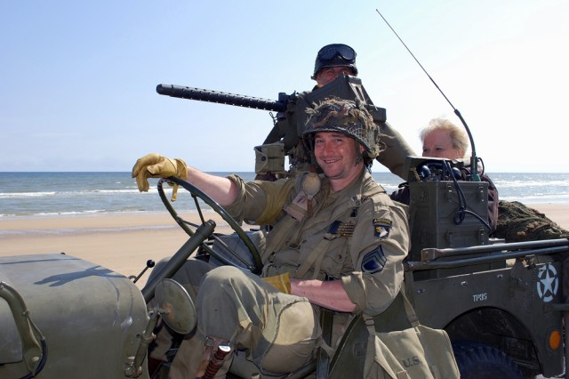 """D-Day participants from Holland dress in WW II garb and ride around in a vintage jeep along Omaha beach here on June 6. """""""