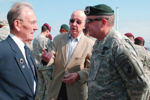 """Maj. Gen. David A. Morris (right), comanding general for the U.S. Army Civil Affairs and Psychological Operations Command (Airborne), is introduced to British WWII Veteran Geoff Noble (left) by his son Chris Noble here on June 4. Noble was a Royal Navy Wireman onboard Landing Craft Tank 1038 on Gold Beach on June 6, 1944. """""""