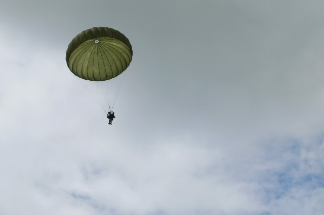 """A paratrooper lands near the La Merderet River by La Fiere bridge commemorating the 65th D-Day Anniversary ceremonies on June 6. Around 300 American, British, French and German paratroopers jumped to commemorate the airborne drop 65-years ago. The ceremony, held at the Iron Mike statue, was highlighted by the presence of over 25 Second World War veterans who participated in an airborne wing exchange between German and American paratroopers. """""""