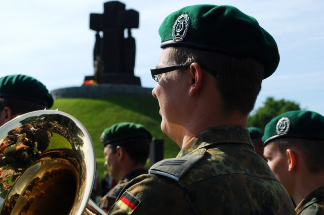 """A German band member and Soldier observes the solemn ceremony at the German cemetery on June 4. Over 200 people attended the commemoration service including American, German, British and French Soldiers. """""""