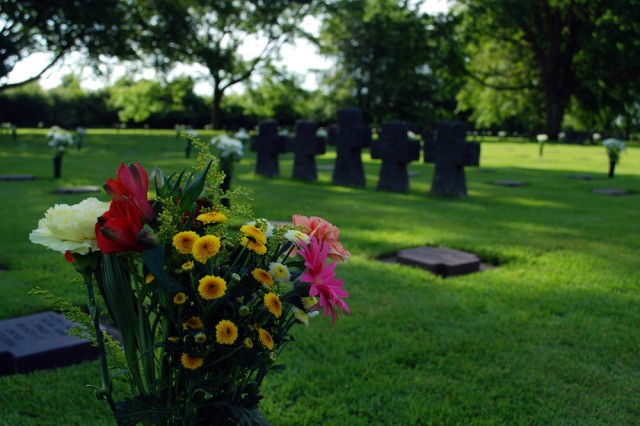 """Flowers and tombstones are the solemn reminders that honor fallen German soldiers on June 4. Over 200 people attended the commemoration service including American, German, British and French Soldiers. """""""