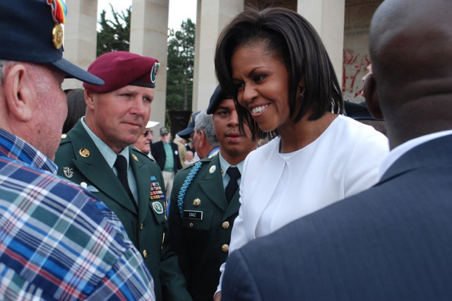 """First Lady Michelle Obama greets a World War II veteran while Sgt. Major Brian Card looks on at the 65th D-Day Anniversary ceremonies at Colleville Sur Mer, France, on June 6. Card, an Army Reserve Soldier, was escorting veterans at the event. He is assigned to the U.S. Army Civil Affairs and Psychological Operations Command (Airborne), located At Fort Bragg, N.C. """""""