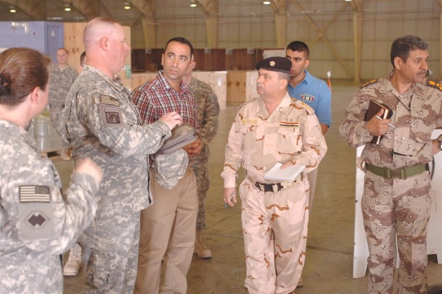 Maj. Robert Frank, 259th Combat Sustainment Support Battalion support operations officer, briefs Staff Maj. Gen. Muniem, the Iraqi Army Director of Electrical and Mechanical Engineering, on the 3d Sustainment Command Expeditionary logistics processes practiced in the consolidated supply support activity warehouse at Joint Base Balad, Iraq, June 2.