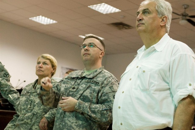 Gen. Ann E. Dunwoody left, the commanding general of Army Materiel Command, and Mr. Dean G. Popps far right, the Acting Assistant Secretary of the Army for Acquisitions, Logistics and Technology, are briefed by Lt. Col. Christopher D. Hardin center, the distribution management center chief for 3d ESC, during a tour of the 3d Sustainment Command Expeditionary Fusion Cell on June 4.
