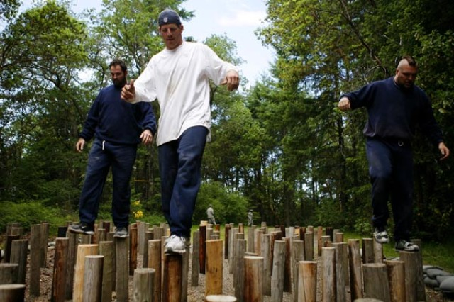 Football-player Brian Russell maneuvers through an obstacle with two teammates on a course at Fort Lewis, Wash., during a team-building visit by the Seattle Seahawks, June 4.
