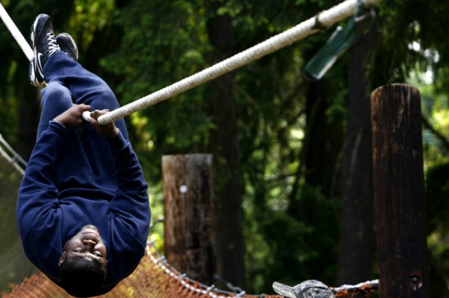 Football-player Justin Forsett slides down a rope on the confidence course at Fort Lewis, Wash., during a team-building visit by the Seattle Seahawks, June 4.