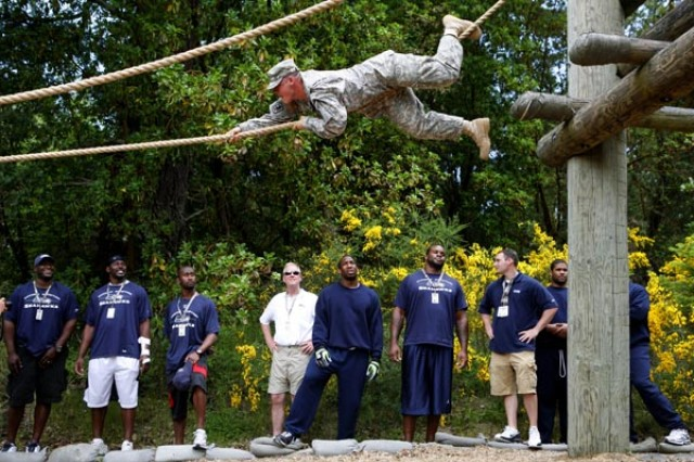 A Soldier from 595th Military Police Company maneuvers across an obstacle during a team-building visit by the Seattle Seahawks, June 4, on Fort Lewis, Wash.