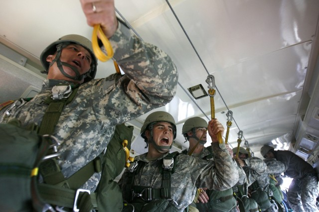 Soldiers echo the commands of a jumpmaster prior to exiting a C-23 Sherpa.