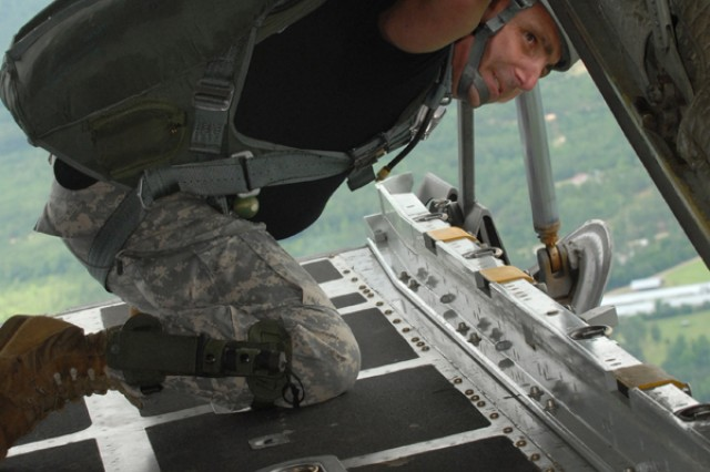 Staff Sgt. Monte Henderson, jumpmaster assigned to Headquarters, Headquarters Company, U.S. Army Civil Affairs and Psychological Operations Command (Airborne) at Fort Bragg, N.C., watches for the drop zone from the ramp of a C-130 aircraft. Approximately 60 Soldiers participated in the airborne operation on Sicily Drop Zone, D-Day 2009.