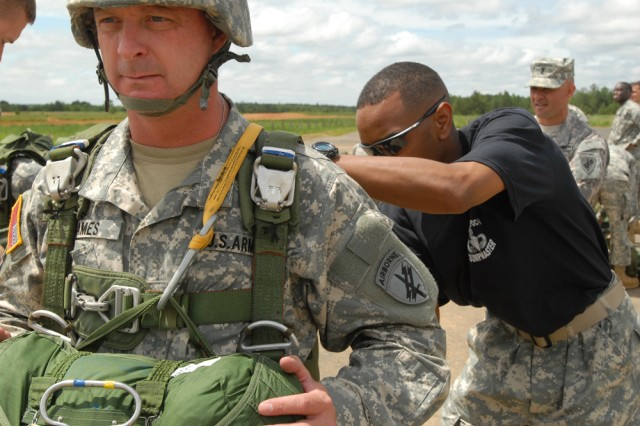 Master Sgt. Dwight Simon, jumpmaster assigned to Headquarters, Headquarters Company, U.S. Army Civil Affairs and Psychological Operations Command (Airborne) at Fort Bragg, N.C., conducts Jumpmaster Personnel Inspection on 1st Sgt. Stuart James prior to an Air Operation on Sicily Drop Zone, D-Day 2009.
