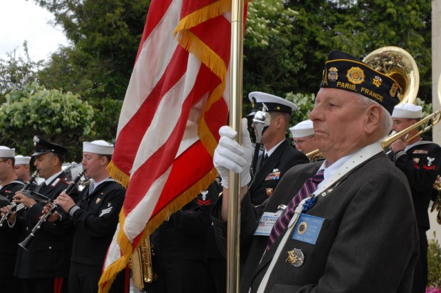 Pierre L. Porter, liaison officer for the American Legion in Paris presents the colors during a ceremony in honor of D-Day veterans in Sainte Mere Eglise, France, June 7. Saint Mere Eglise was the first town liberated by American forces on D-Day.
