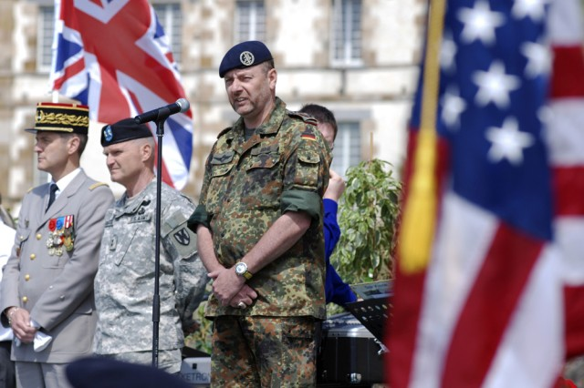 Germany's military attaché to France, Army Col. Christian Duhr, addresses servicemembers and veterans from the United States, France and Germany, as well as hundreds of others who attended a ceremony at Mont Saint Michel, France, June 4, honoring the 65th anniversary of the allied invasion of Normandy. Maj. Gen. Yves Fontaine, commander of U.S. Army Europe's 21st Theater Sustainment Command (center) and French Army Gen. Pierre Barbaud (left) also spoke at the ceremony.