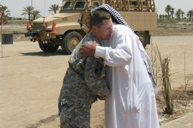 Col. Robert Schmitt, the 287th Sustainment Brigade commander, and Shaykh Ali Mohamed Al Manshed of the AL Ghizi tribe, exchange farewells after luncheon at the shaykh's mudhif, or tribal council hall, in Al Manshed village May 21.