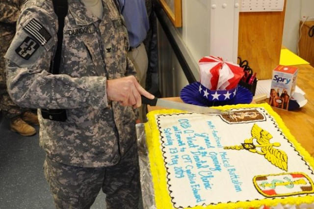 Col. Thomas Dundon, commander, 360th Medical Company, who traveled from Joint Base Balad, celebrates the grand opening of the Q-West Dental Clinic by cutting a cake at Contingency Operating Base Q-West, Iraq May 23.