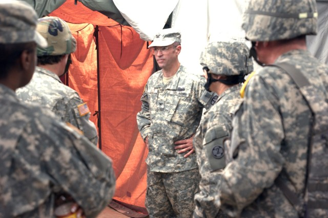 FORT HUNTER LIGGETT, Calif - Army Col. (P) Bryan Kelly (center), Medical Readiness Training Command incoming commander, visits the Global Medic training site here, June 9.  Kelly, an East Sandwich, Mass., native, talks with members of both the training and operational teams to ensure the operation run smoothly. The Medical Readiness Training Command is based at Fort Sam Houston, San Antonio.