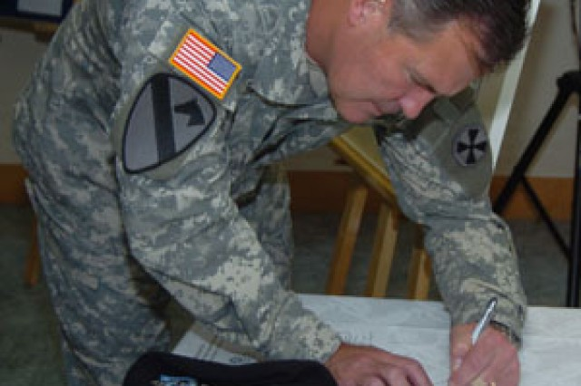 Eighth U.S. Army Commander Lt. Gen. Joseph Fil Jr. signs the letter he stamped with the first commemorative postmark honoring the 8th Army's 65th anniversary.
