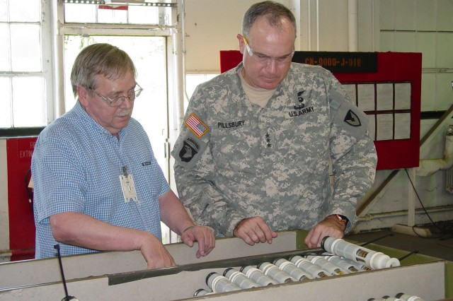 AMC Deputy Commanding General Lt. Gen. James Pillsbury receives a briefing about the 30mm recovery program from CAAA Explosives Operator Supervisor Mark Ross.