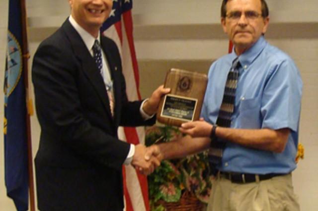 Mr. Jyuji Hewitt, Deputy to JMC commanding general, presents Mr. Terry Trivitt with his award.