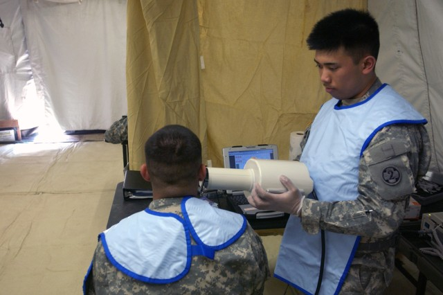 FORT HUNTER LIGGETT, Calif. - Army Pvt. 1st Class Juan C. Enriquez (left), 349th Combat Support Hospital, participates as Spc. Timothy Cirera (right), 307th Medical Company (Dental Services), takes dental X-rays with a new digital X-ray unit called DEXIS. The Soldiers are part of the U.S. Army Reserve Command's Global Medic joint training event, which provides units with the opportunity to execute various medical tasks in a combat environment. The 307th is based out of Valejo, Calif. and the 349th is based out of Bell, Calif.