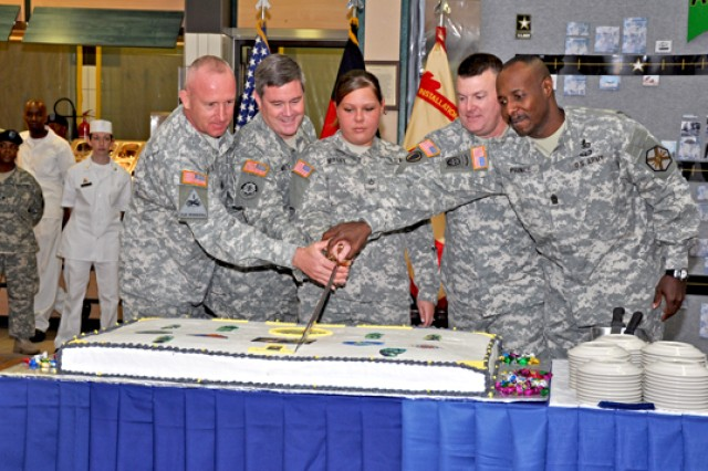 Command Sgt. Maj. Roger Blackwood (from left), Maj. Gen. Terry Wolff, Pfc. Brittany Marky, Col. Jeffrey Dill and Command Sgt. Maj. Hector Prince slice an Army Birthday cake during an event in the Wiesbaden Dining Facility June 11.