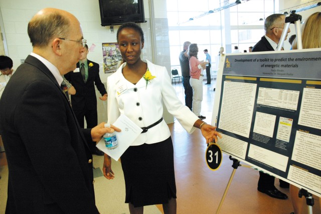 Nadja Rhodes, an Aberdeen High School senior who attends the Science and Mathematics Academy, explains her project to Albert Price, a parent of an SMA student, during SMA's gallery walk of senior capstone projects May 19.
