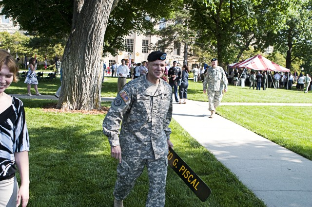 As he leaves the change of command ceremony June 5, outgoing Garrison Commander Col. Richard Piscal carries the sign bearing his name that hung in front of the garrison headquarters building during his command.