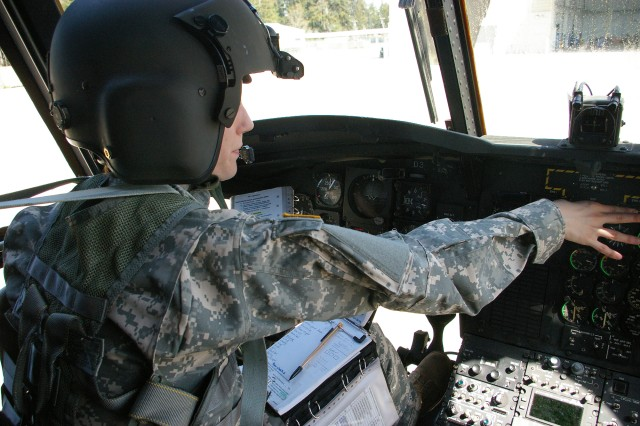 Lt. Heather Cupitt conducted a preflight inspection of a Chinook helicopter at Fort Lewis WA. Cupitt said while there are similarities between flying an airplane and a helicopter, one of the many differences is that her pre-flight for the helicopter takes much longer.