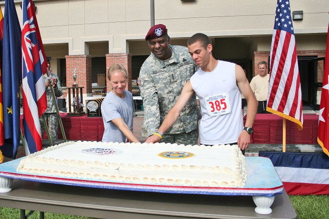Lt. Gen. Lloyd J. Austin III, commander XVIII Airborne Corps cuts Fort Bragg's U.S. Army birthday cake with teh winners of Fort Bragg's Army Birthday 10-miler race, U.S. Military Academy at West Point cadet Alexis Santiago (right) and Nicole Smith of the 3rd Battalion, 4th Air Defense Artillery Regiment.