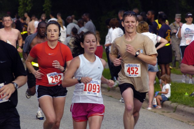 Jessica Roberts, 1093, crosses the finish line, trailed by Bridget Hidalgo, 282 and Nathan Huff, 452 during the 13th Annual Army Birthday 10-Mile race at Fort Bragg Thursday. Nicole Smith, not pictured, took first place in the women's division with a time of 1:11:42. More than 1800 runners participated in this year's event.