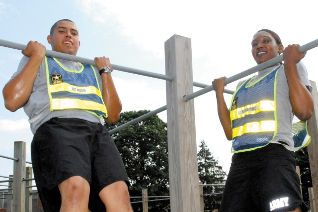 Sergeants Jason Bedoya, left, and Gabrielle Martinez work out on the pull-up bar.