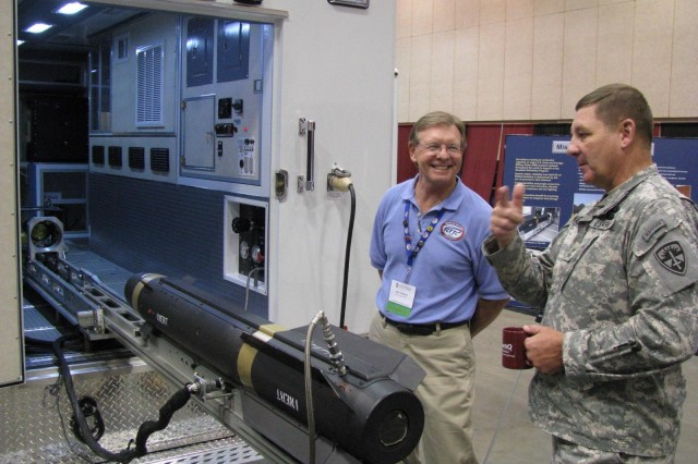 Maj. Gen. Roger Nadeau, commander of Army Test and Evaluation, talks with John Aufderhar of the Redstone Technical Test Center about the missile surveillance testing vehicles used to test Hellfire (pictured), Longbow and a host of other missiles. Nadeau was a panel participant during the 11th annual Test Week.