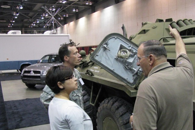 Robert Nicholson, right, of Redstone Arsenal's Target Management Office, shows Lt. Col. Todd Minners of the Office of the Deputy Under Secretary of the Army with oversight of the Test and Evaluation Office, and Abigail Maul of the Navy's InterTec project, the special features of a door on the Russian BTR-80 armored personnel carrier. The Target Management Office, which has a fleet of foreign military equipment that is used in testing U.S. artillery systems, was among about 100 exhibitors at Test Week 2009.