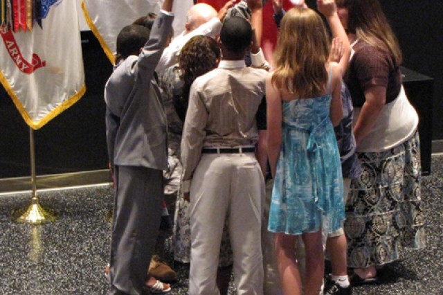 """Ceremony speaker Brig. Gen. Genaro Dellarocco has the Space Camp scholarship recipients huddle with him. At his request, they then run over to hug program creator Evelyn Fox who started the program in 1984. """"The best thing about it (Space Camp) is that it's fun,"""" Dellarocco told the children."""