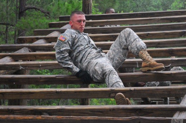 """Specialist Dustin McBroom, Battery A, maneuvers through the """"weaver,"""" at the Fort Stewart Confidence Obstacle Course. The weaver is a task that tests Soldiers' strength and endurance by going under, then over wooden beams."""