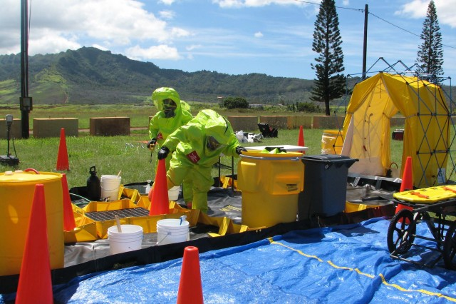 """Two Soldiers of the """"Tropic ARC Team"""" conduct decontamination operations during their certification lanes."""
