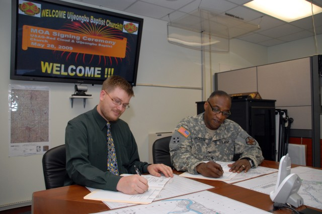 "Signing a Memorandum of Understanding for the Conduct of Public Affairs Operations are Thomas Vasel (left), pastor of Uijeongbu Baptist Church, and Col. Larry ""Pepper Jackson, U.S. Army Garrison-Red Cloud commander. The MOU, signed May 28, establishes a working relationship between USAG-Red Cloud and Uijeongbu Baptist Church for the use of church facilities as necessary to host press conferences and interviews when such functions could hinder essential operations on post. Jackson thanked Pastor Vasel for his willingness to support Soldiers and Families as a part of the overall community."